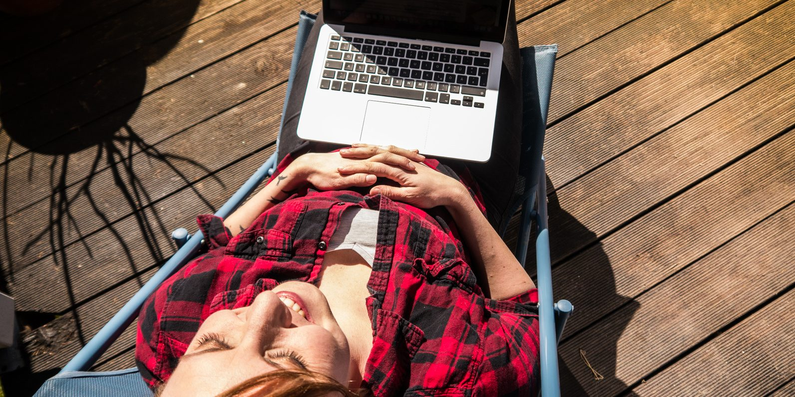 Home office: Young woman working while sitting on a patio with her laptop